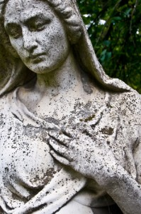 detail of an old tombstone showing a grieving woman